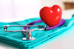 Stethoscope shaping heart and clipboard on medical uniform, closeup. A stethoscope shaping a heart and a clipboard on a medical uniform, closeup royalty free stock images