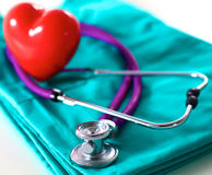 Stethoscope shaping heart and clipboard on medical uniform, closeup. A stethoscope shaping a heart and a clipboard on a medical uniform, closeup royalty free stock photography
