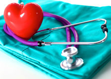 Stethoscope shaping heart and clipboard on medical uniform, closeup. A stethoscope shaping a heart and a clipboard on a medical uniform, closeup stock photography