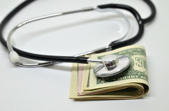 Stethoscope sitting on US dollar bills Royalty Free Stock Images