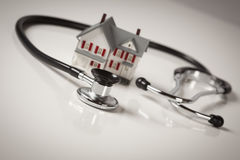 Stethoscope with Small Model Home. Stethoscope and Model House on Gradated Background with Selective Focus Stock Photo