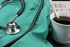 Stethoscope with smock, coffee & keyboard. Royalty Free Stock Photo