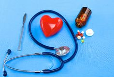 Stethoscope and some pills -  on a blue background Royalty Free Stock Images