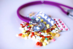 Stethoscope and some pills - isolated on a white background Stock Images