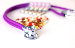 Stethoscope and some pills - isolated on a white background Stock Photo