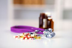 Stethoscope and some pills -  on a white background Stock Photos