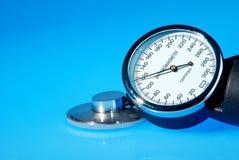 Stethoscope and sphygmomanometer. On blue background stock image