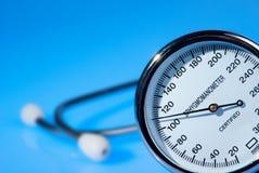 Stethoscope and sphygmomanometer on blue. Background stock photos