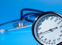 Stethoscope and sphygmomanometer on blue. Background stock images