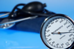 Stethoscope and sphygmomanometer on blue background. With shallow depth of field stock image