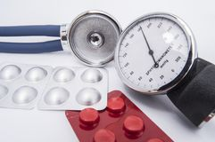 Stethoscope and sphygmomanometer dial with high indicators of arterial blood pressure lie on the white medical table near the pill. S and medicines in a red and stock photo