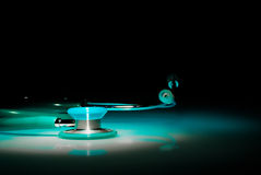Stethoscope in a spotlight on blue reflective table Royalty Free Stock Image