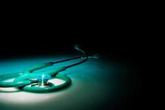 Stethoscope in a spotlight on blue reflective table Royalty Free Stock Images