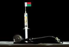 Stethoscope and syringe filled with drugs injecting the Malagasy flag on a black background Royalty Free Stock Photos