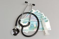 Stethoscope, syringe and money on gray. Background Stock Photo