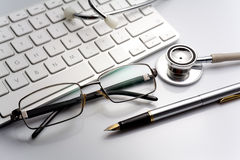 Stethoscope on a table with keyboard and glasses Royalty Free Stock Photography