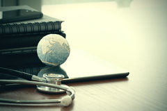 Stethoscope and texture globe with digital tablet Stock Images