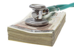 Stethoscope on the top of the money. Selective focus on stethoscope. It could describe high cost of medicine or bribe in medicine stock photography