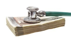 Stethoscope on the top of the money. Selective focus on stethoscope. It could describe high cost of medicine or bribe in medicine royalty free stock photo