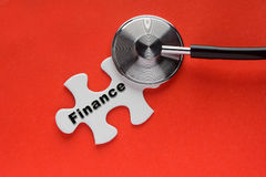Stethoscope on top of a white jigsaw puzzle with a written word. Finance on a red background. Conceptual of a financial rescue Stock Image