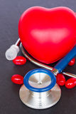 Stethoscope with two red hearts and pills Stock Images