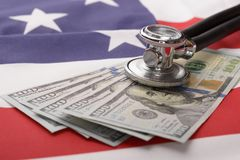 Stethoscope on us currency and american flag Royalty Free Stock Photography