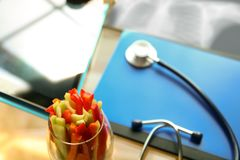 Stethoscope, vegetable and x-ray in the office. stock photography