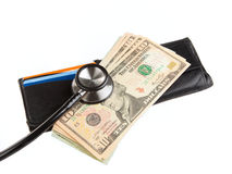 Stethoscope on a wallet with dollars. Financial health check: Stethoscope on wallet with stack of ten dollar bills Royalty Free Stock Photos