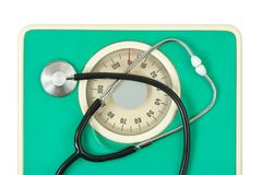 Stethoscope on weight scale Royalty Free Stock Images