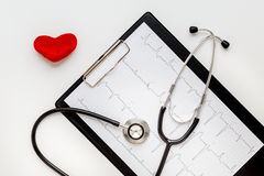 Stethoscope on white background with plush heart and cardiogram Royalty Free Stock Photos