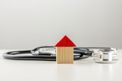 Stethoscope with a wooden model of a house Royalty Free Stock Photos