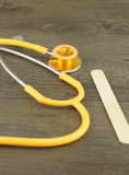 Stethoscope and wooden tongue depressor Royalty Free Stock Images