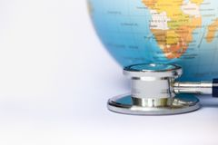 Stethoscope wrapped around globe on white background. earth day. stock photos