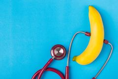 Stethoscope and yellow banana on blue background. For men penis. Close up Stethoscope and yellow banana on blue background. For men penis check up concept. With Royalty Free Stock Images