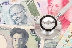 Stethoskop auf asiatischer Banknote Stockbilder
