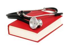 Stethoskop auf dem roten Buch Stockfotos