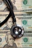 Stethoskop auf einem Hintergrund von $20 Rechnungen Stockfotografie