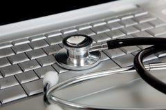 Stethoskop auf einer Laptop-Computer Stockfotos