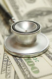 Stethoskop auf Geldhintergrund und -pillen Lizenzfreies Stockfoto