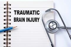Stethoskop auf Notizbuch und Bleistift mit traumatischem Brain Injury lizenzfreie stockfotografie