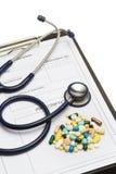 Stethoskop auf Verordnung und Pillen auf weißem Hintergrund stockfotografie