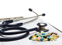 Stethoskop auf Verordnung und Pillen auf weißem Hintergrund stockfotos