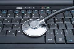 Stethoskop, das auf Computer legt Stockbilder