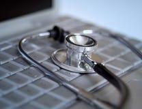 Stethoskop, das auf Computer legt Stockbild