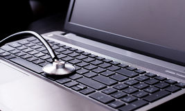 Stethoskop, das auf einer Computertastatur stillsteht - Stockbild