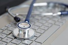 Stethoskop, das auf Laptoptastaturnahaufnahme liegt Lizenzfreies Stockfoto