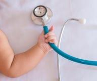 Stethoskop der medizinischen Instrumente in der Hand des neugeborenen Babys Stockbild