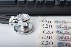 Stethoskop, Geld, Tastatur auf weißem, medizinischem Konzept Lizenzfreie Stockbilder