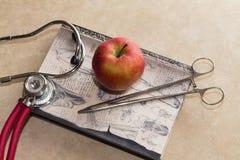 Stethoskop, medizinische Klammer, medizinisches Buch und roter Apfel Stockbild