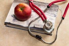 Stethoskop, medizinisches Buch und roter Apfel Stockfotos